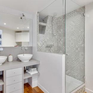 Réalisation d'une salle de bain design avec un placard à porte plane, des portes de placard blanches, une douche d'angle, un carrelage gris, un mur gris, un sol en bois brun, une vasque, un sol marron, une cabine de douche à porte battante et un plan de toilette gris.