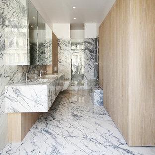 Exemple d'une grand salle de bain tendance avec un WC suspendu, des dalles de pierre, un lavabo intégré, un plan de toilette en marbre, un carrelage gris et un carrelage blanc.