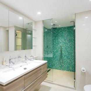 Idées déco pour une grand salle de bain contemporaine avec un placard à porte plane, des portes de placard beiges, un WC suspendu, un carrelage vert, un mur beige, un sol en carrelage de porcelaine, un lavabo intégré, un sol beige, une cabine de douche à porte battante et un plan de toilette blanc.