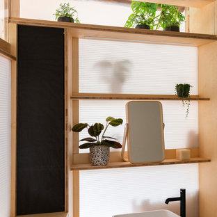 Inspiration för ett litet funkis en-suite badrum, med luckor med profilerade fronter, svarta skåp, ett badkar i en alkov, en dusch/badkar-kombination, en vägghängd toalettstol, vit kakel, vita väggar, bambugolv, ett fristående handfat, träbänkskiva och dusch med gångjärnsdörr