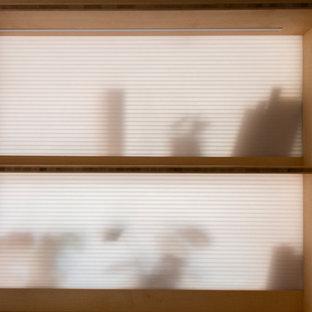 Diseño de cuarto de baño principal, contemporáneo, con puertas de armario negras, bañera empotrada, combinación de ducha y bañera, sanitario de pared, baldosas y/o azulejos blancos, baldosas y/o azulejos de cerámica, paredes blancas, suelo de bambú, lavabo sobreencimera, encimera de madera y ducha con puerta con bisagras