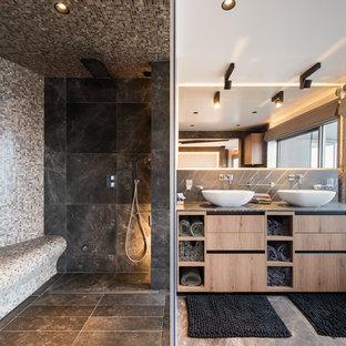 Idées déco pour une salle de bain principale contemporaine de taille moyenne avec un placard à porte plane, des portes de placard en bois brun, une douche d'angle, un carrelage noir, une vasque, un sol gris, une cabine de douche à porte battante et un plan de toilette gris.
