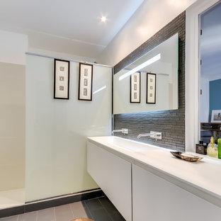 Cette photo montre une salle de bain tendance de taille moyenne avec un carrelage gris, un carrelage de pierre, un mur blanc et un lavabo intégré.