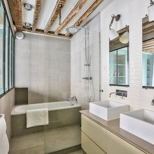Exemple d'une salle de bain principale scandinave de taille moyenne avec un placard à porte plane, des portes de placard jaunes, une baignoire en alcôve, un espace douche bain, un carrelage gris, une vasque, un sol gris, aucune cabine et un plan de toilette beige.