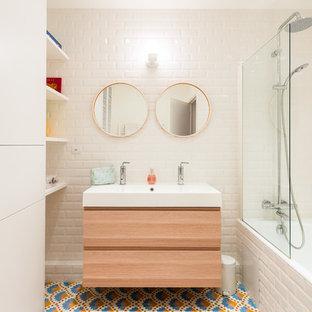 Cette image montre une salle de bain nordique de taille moyenne pour enfant avec des carreaux de céramique, un mur blanc, un sol en carreaux de ciment, un plan vasque, un placard à porte plane, des portes de placard en bois clair, un combiné douche/baignoire, un carrelage blanc, un sol multicolore, aucune cabine et une baignoire en alcôve.