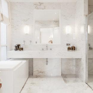 Cette image montre une grande douche en alcôve principale design avec un carrelage blanc, des dalles de pierre, un sol en marbre, un mur blanc, un lavabo encastré et un plan de toilette en marbre.