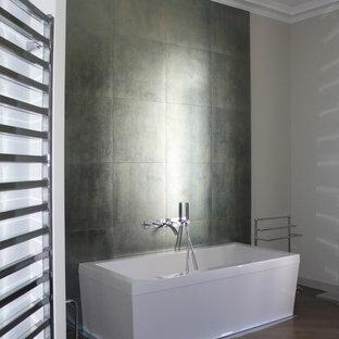 Inspiration pour une salle de bain principale minimaliste de taille moyenne avec un carrelage gris, un mur blanc, un sol en bois foncé et une baignoire indépendante.