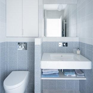 Imagen de cuarto de baño con ducha, escandinavo, pequeño, con armarios abiertos, baldosas y/o azulejos azules, baldosas y/o azulejos grises, suelo de cemento, lavabo suspendido, suelo gris, sanitario de pared, puertas de armario blancas y paredes blancas