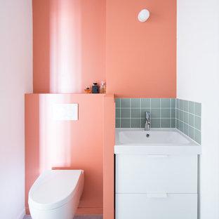 Foto di una piccola stanza da bagno padronale scandinava con ante bianche, WC sospeso, piastrelle bianche, piastrelle rosa, piastrelle a listelli, pareti bianche, pavimento in cemento, lavabo sottopiano e pavimento grigio