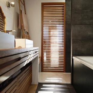 Ejemplo de cuarto de baño principal, contemporáneo, pequeño, con armarios con puertas mallorquinas, bañera encastrada sin remate, ducha empotrada, sanitario de pared, baldosas y/o azulejos negros, losas de piedra, paredes blancas, suelo de madera clara, lavabo encastrado, encimera de madera y suelo negro