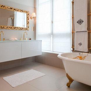 Réalisation d'une salle de bain principale design de taille moyenne avec des portes de placard blanches, une baignoire sur pieds, un mur beige, un plan de toilette en verre, un carrelage beige, des carreaux de céramique, un sol en carrelage de céramique, un lavabo suspendu et un sol beige.