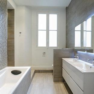 Réalisation d'une salle de bain principale design de taille moyenne avec des portes de placard blanches, une baignoire posée, un mur blanc, un sol en carrelage de céramique, un lavabo intégré, un placard à porte plane, un carrelage gris, un WC suspendu et un carrelage de pierre.