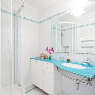 Ejemplo de cuarto de baño con ducha, actual, de tamaño medio, con lavabo bajoencimera, armarios con paneles lisos, encimera de vidrio, ducha esquinera, baldosas y/o azulejos blancos, paredes blancas, suelo de baldosas de porcelana, puertas de armario blancas y encimeras azules