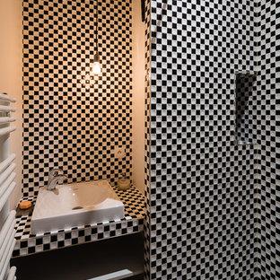 Aménagement d'une petit salle d'eau contemporaine avec une vasque, un placard sans porte, un mur blanc, carrelage en mosaïque, des portes de placard blanches et un carrelage noir et blanc.