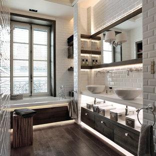 Réalisation d'une salle de bain principale nordique avec un placard à porte plane, des portes de placard en bois sombre, une baignoire en alcôve, un carrelage blanc, un carrelage métro, un mur blanc, un sol en bois foncé, une vasque et un sol marron.