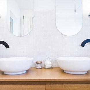 Inspiration pour une salle de bain principale design de taille moyenne avec des portes de placard en bois brun, un carrelage blanc, carrelage en mosaïque, un mur blanc, une vasque et un plan de toilette en bois.