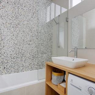 Inspiration pour une salle de bain design de taille moyenne pour enfant avec des portes de placard marrons, une baignoire encastrée, un carrelage vert, un mur beige, un sol en terrazzo, un lavabo posé et un plan de toilette beige.
