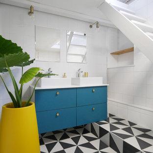 Exemple d'une salle de bain tendance avec un placard à porte plane, des portes de placard bleues, un carrelage blanc, un mur blanc, une vasque et un plan de toilette blanc.