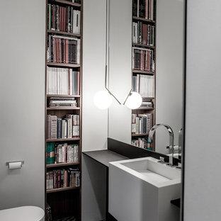 Cette photo montre une salle de bain tendance de taille moyenne avec un WC suspendu, un carrelage noir et blanc, un carrelage gris, un mur blanc, un placard sans porte, des portes de placard en bois brun, un lavabo suspendu et un plan de toilette en bois.