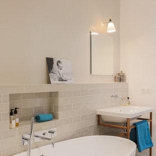 Inspiration pour une salle d'eau design de taille moyenne avec un combiné douche/baignoire, un mur beige, un sol beige, aucune cabine, une baignoire indépendante, un carrelage beige et un lavabo suspendu.