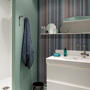 Cette image montre une salle d'eau design avec un placard à porte plane, des portes de placard blanches, une douche ouverte, un mur multicolore, un lavabo intégré et aucune cabine.
