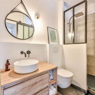 Cette image montre une salle de bain design de taille moyenne avec un placard à porte plane, des portes de placard beiges, un WC suspendu, un carrelage gris, des carreaux de porcelaine, un mur blanc, une vasque, un plan de toilette en bois, un sol gris, aucune cabine et un plan de toilette beige.
