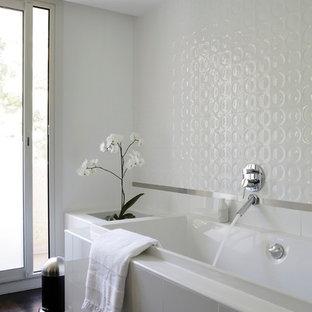 Cette image montre une salle de bain principale design de taille moyenne avec une baignoire posée, un carrelage blanc, un mur blanc et un sol en bois foncé.