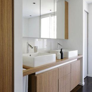 Idée de décoration pour une salle de bain design de taille moyenne avec une vasque, un placard à porte plane, des portes de placard en bois brun, un mur blanc et un sol en bois foncé.