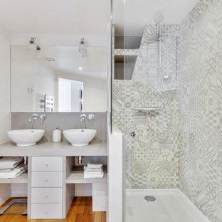 Inspiration pour une salle de bain design avec des portes de placard noires, un carrelage gris, un mur blanc, un sol en bois brun, une vasque, un sol marron, un plan de toilette gris et meuble double vasque.