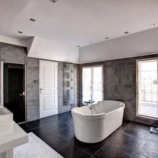 Idées déco pour une grand douche en alcôve principale contemporaine avec un lavabo suspendu, une baignoire indépendante, un carrelage gris, un mur gris et des portes de placard blanches.