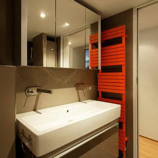 Exemple d'une salle d'eau tendance avec des portes de placard grises, un mur marron, un sol en carrelage de céramique et une grande vasque.