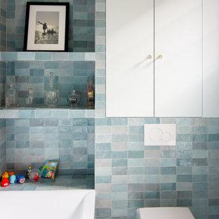 Idéer för ett mellanstort blå en-suite badrum, med blå skåp, ett undermonterat badkar, en vägghängd toalettstol, blå kakel, keramikplattor, blå väggar, ett nedsänkt handfat, kaklad bänkskiva och beiget golv