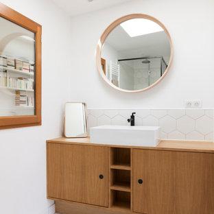 Cette image montre une salle de bain design avec un placard à porte plane, des portes de placard en bois brun, un carrelage blanc, un mur blanc, une vasque, un plan de toilette en bois, un sol blanc, meuble simple vasque, une douche ouverte, un WC suspendu, des carreaux de céramique, un sol en carrelage de céramique, un plan de toilette blanc et meuble-lavabo sur pied.