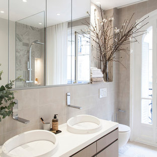 Scandinavian bathroom in Paris with flat-panel cabinets, light wood cabinets, a wall-mount toilet, beige tile, beige walls, a vessel sink and white benchtops.