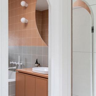 Cette image montre une salle de bain design avec un placard à porte plane, des portes de placard oranges, un carrelage gris, un carrelage orange, une vasque, un sol blanc, un plan de toilette orange et meuble simple vasque.