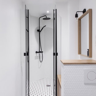 Cette photo montre une douche en alcôve tendance avec un placard à porte plane, des portes de placard en bois clair, un carrelage blanc, un mur blanc, un plan de toilette en bois, un sol multicolore, une cabine de douche à porte battante et un plan de toilette beige.