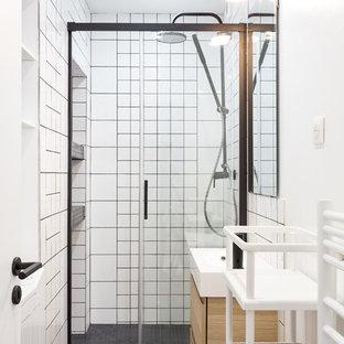 Cette photo montre une salle de bain scandinave avec un placard à porte plane, des portes de placard en bois clair, un carrelage blanc, des carreaux de céramique, un mur blanc, un lavabo suspendu, un sol gris et une cabine de douche à porte coulissante.