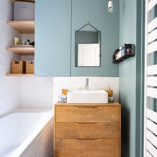 Cette photo montre une petit salle de bain principale scandinave avec des portes de placard en bois brun, une baignoire posée, un carrelage blanc, un mur bleu, une vasque, un plan de toilette en bois, un sol multicolore, un placard à porte plane, un combiné douche/baignoire, un WC suspendu, un carrelage métro, un sol en carreaux de ciment, aucune cabine et un plan de toilette marron.