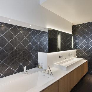 Idées déco pour une grand douche en alcôve principale contemporaine avec des portes de placard en bois clair, une baignoire encastrée, un carrelage gris, carrelage en mosaïque, un mur blanc, un sol en carrelage de céramique, une grande vasque, un plan de toilette en surface solide et un placard à porte plane.