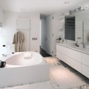 Cette photo montre une grand salle de bain principale tendance avec des portes de placard blanches, une baignoire indépendante, un carrelage de pierre, un mur blanc, un lavabo intégré et un sol en marbre.