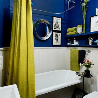Imagen de cuarto de baño contemporáneo, pequeño, con armarios abiertos, bañera con patas y paredes azules