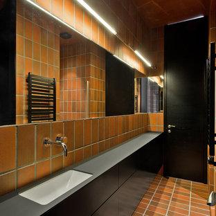 Ispirazione per una stanza da bagno industriale con piastrelle marroni, piastrelle a listelli, pareti marroni, pavimento in mattoni, lavabo sottopiano e pavimento marrone