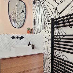 Cette photo montre une salle de bain scandinave avec un placard à porte plane, des portes de placard en bois clair, un carrelage blanc, un mur rose, une vasque et un plan de toilette blanc.