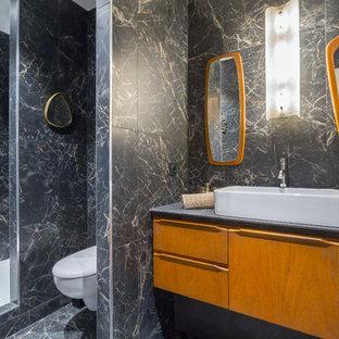 Cette photo montre une salle de bain rétro avec un placard à porte plane, des portes de placard en bois brun, un WC suspendu, un carrelage noir et blanc, un carrelage gris, une vasque, un sol noir, aucune cabine et un plan de toilette gris.