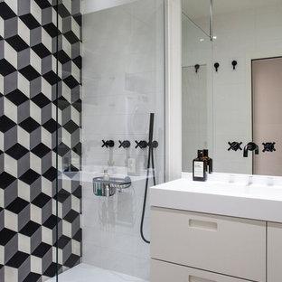 Inspiration pour une salle d'eau design avec un placard à porte plane, des portes de placard blanches, un carrelage noir et blanc, un lavabo intégré, un sol gris et un plan de toilette blanc.