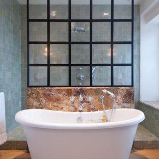 Cette image montre une salle de bain principale bohème de taille moyenne avec une baignoire indépendante, une douche ouverte, un carrelage bleu, un mur bleu, un sol en bois clair et aucune cabine.