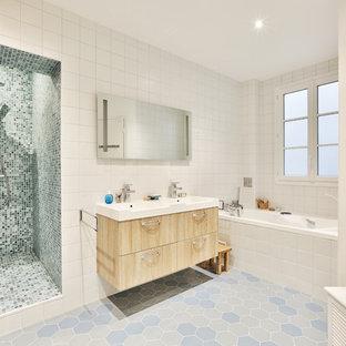 Cette image montre une grand salle de bain principale traditionnelle avec des portes de placard en bois clair, une douche à l'italienne, un carrelage blanc, un mur blanc, un sol en carrelage de céramique, un sol bleu, une cabine de douche à porte battante, des carreaux de céramique, un placard à porte affleurante, un bain bouillonnant, un WC suspendu, un lavabo intégré, un plan de toilette en surface solide et un plan de toilette blanc.