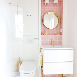 Small cottage chic master pink tile and mosaic tile terrazzo floor and multicolored floor corner shower photo in Paris with beaded inset cabinets, white cabinets, a wall-mount toilet, white walls, a pedestal sink, tile countertops, a hinged shower door and pink countertops