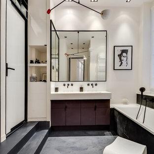 Bild på ett stort funkis vit vitt en-suite badrum, med marmorbänkskiva, svart golv, dusch med gångjärnsdörr, vita väggar, betonggolv, luckor med profilerade fronter, svarta skåp, ett undermonterat badkar, en vägghängd toalettstol, vit kakel, spegel istället för kakel och ett avlångt handfat