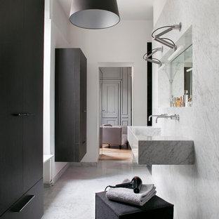 Cette photo montre une salle d'eau tendance de taille moyenne avec des portes de placard noires, des dalles de pierre, un mur gris, un sol en marbre, un lavabo intégré et un plan de toilette en marbre.